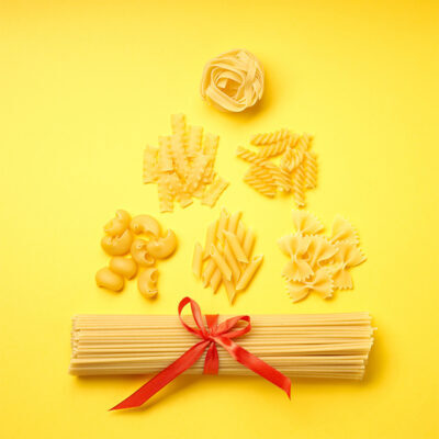 A christmas tree made with various forms of pasta on yellow background. Top view. Copy space for text. Concept.